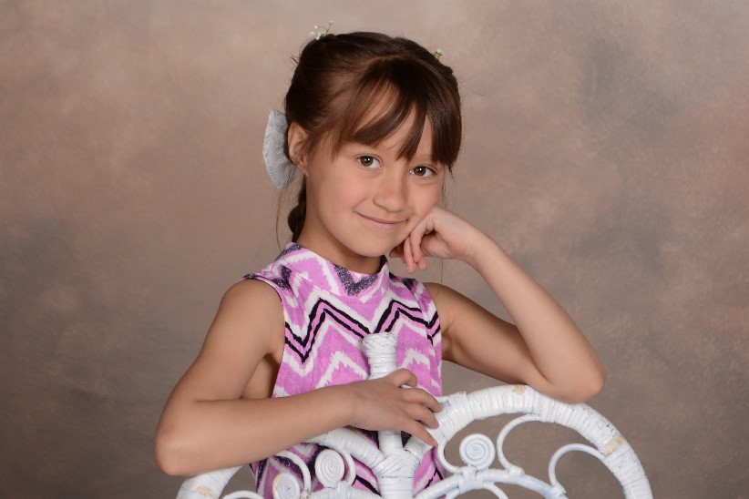 young girl in purple dress smiles for professional photograph taken at andrae michaels portrait studios in colorado springs