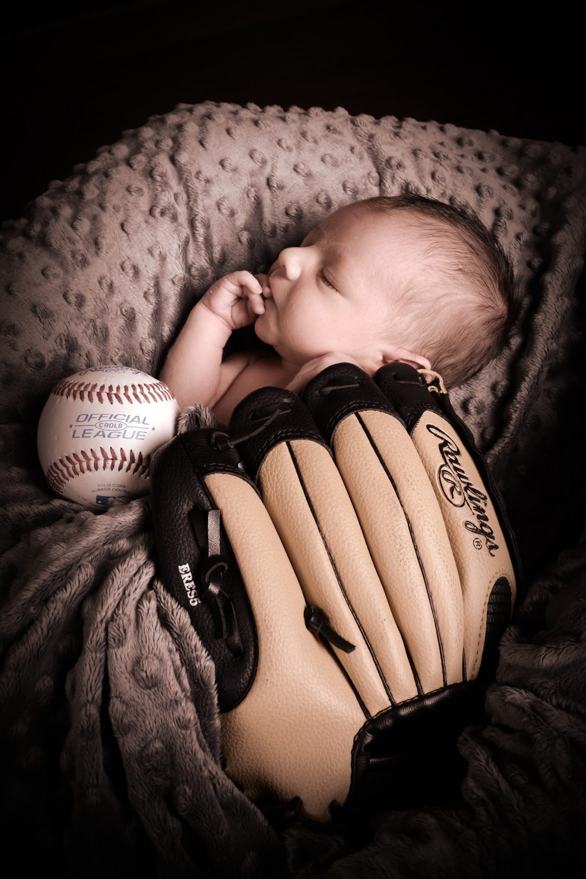 newborn baby with baseball glove and baseball professional portrait taken by andrae michaels photography studios