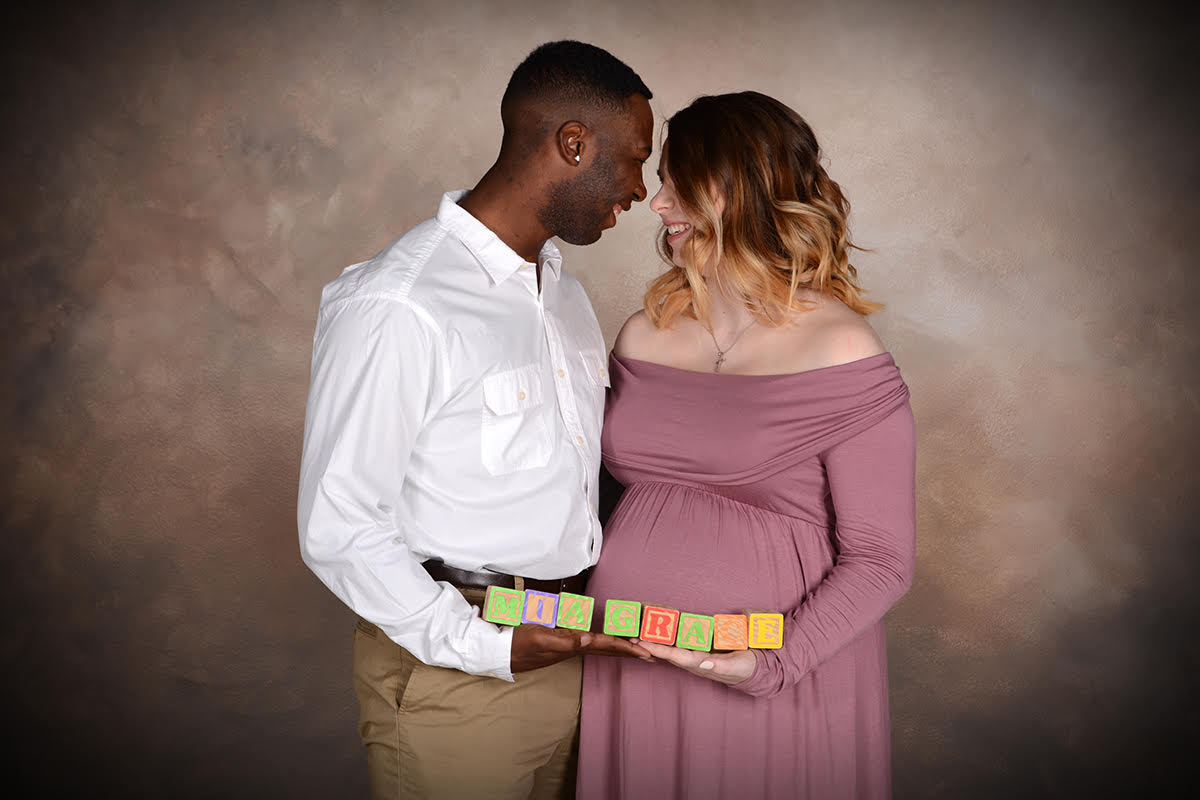 military couple smiles at each other during maternity photography by Andrea Michaels
