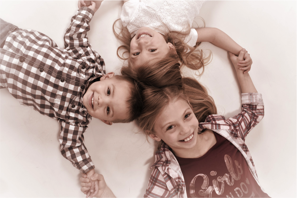 siblings grasp hands in professional studio portrait by Andrae Michaels