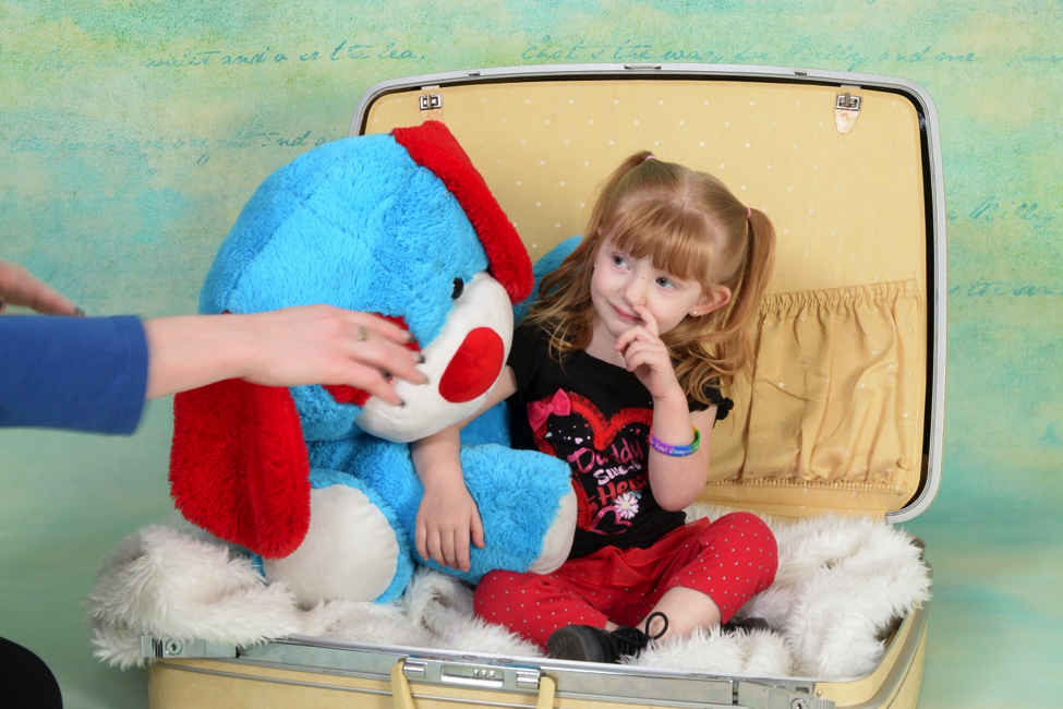 professional photograph of young girl posing with stuffed puppy at Andrea Michaels portrait studios